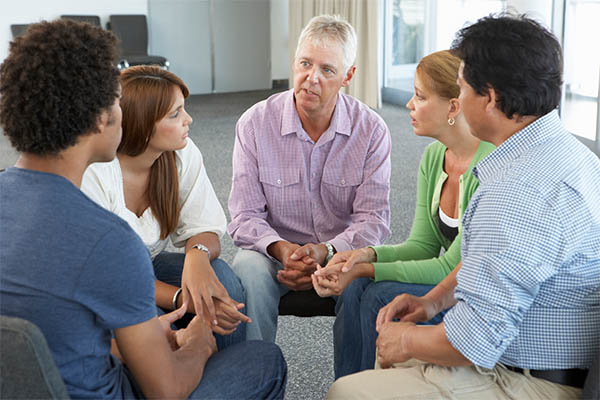 group therapy with five adults in circle